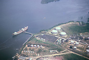Aerial view of large oil tanker ship, docked at jetty of terminal, Manaus, Brazil 1962