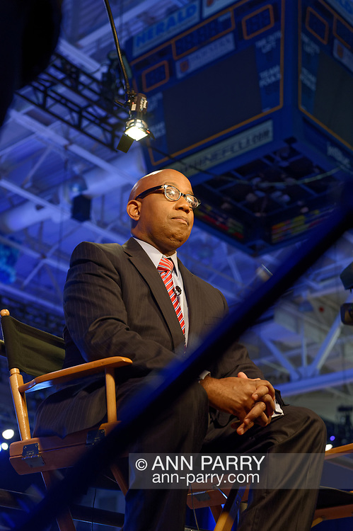 Hempstead, New York, USA. May 23, 2018. Reporter, sitting on media riser, tapes political news segment during Day 1 of New York State Democratic Convention, held at Hofstra University on Long Island.