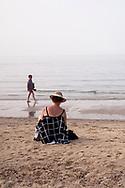 woman sitting on the beach near Oostkapelle on the peninsula Walcheren, Zeeland, Netherlands.<br /> <br /> Frau sitzt am Strand bei Oostkapelle auf Walcheren, Zeeland, Niederlande.