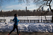 A woman in sports clothes runs along a path that has been cleared from snow in West side Central Park, Manhattan, New York City, New York, United States of America. The city has just had a record breaking snow storm in January 2016.