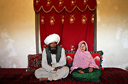 Faiz, 40, and Ghulam, 11, sit in her home prior to their wedding in rural Afghanistan, Sept. 11, 2005. Ghulam said she is sad to be getting engaged as she wanted to be a teacher. Her favorite class was Dari, the local language, before she was made to drop out of school. Married girls are seldom found in school, limiting their economic and social opportunities. Parents sometimes remove their daughters from school to protect them from the possibility of sexual activity outside of wedlock. It is hard to say exactly how many young marriages take place, but according to the Afghan women's ministry and women's NGOs, approximately 57 percent of Afghan girls get married before the legal age of 16. In addition, once the girl's father has agreed to the engagement, she is pulled out of school immediately. Early pregnancies also result in an increase in complications during child birth.