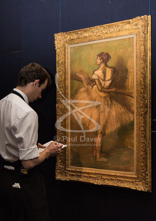 Sotheby's, London, June 19th 2015. International auctioneers Sotheby's gears up to holding what they say is London's highest valued auction of contemporary artworks, to be held on June 24th 2015 where the combined artworks are anticipated to bring in as much as £203 million. PICTURED: A Sotheby's gallery technician examines Edgar Degas' Danseuse a la Barre, pasted on paper wich is expected to ean up to £1.5 million at auction.  // Payment/Licencing/Contact details: Paul@pauldaveycreative.co.uk Tel: 07966016296