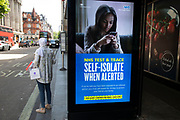 HM Government, Public Health England, NHS advertising boards advice to stay alert to the symptoms as part of the test and trace program as the Coronavirus lockdown measures are set to ease further, the west end starts to fill with people as they return to the shopping district on Oxford Street and the quiet city starts coming to an end on 22nd June 2020 in London, England, United Kingdom. As of today the government has relaxed its lockdown rules, and is allowing some non-essential shops to open with individual shops setting up social distancing queueing systems.