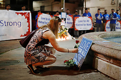 A woman places a flower at a vigil remembering the victims of a shooting on Sunday evening on Danforth, Ave. in Toronto, ON, Canada, on Monday, July 23, 2018. Photo by Mark Blinch/CP/ABACAPRESS.COM