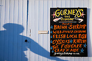 Shop sign for Gurneys Fish Shop - fresh shrimp, salmon, oysters, kippers - in Burnham Market in North Norfolk, UK