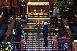 © Licensed to London News Pictures. 25/12/2020. Manchester, UK. A member of the choir lights the centre candle over the advent wreath during the service . Approximately forty people , including the choir , clergy and parishioners , attend the traditional Christmas Day service at St Ann's Church in St Ann's Square Manchester on the morning of Christmas Day 2020 . In previous years it's estimated that the church's capacity of approximately two hundred would be met . Photo credit: Joel Goodman/LNP