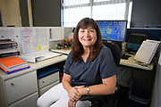 Woman sitting in her cubicle at her office in at a Florida Utility. Part of a corporate library of images for internal and external communications.