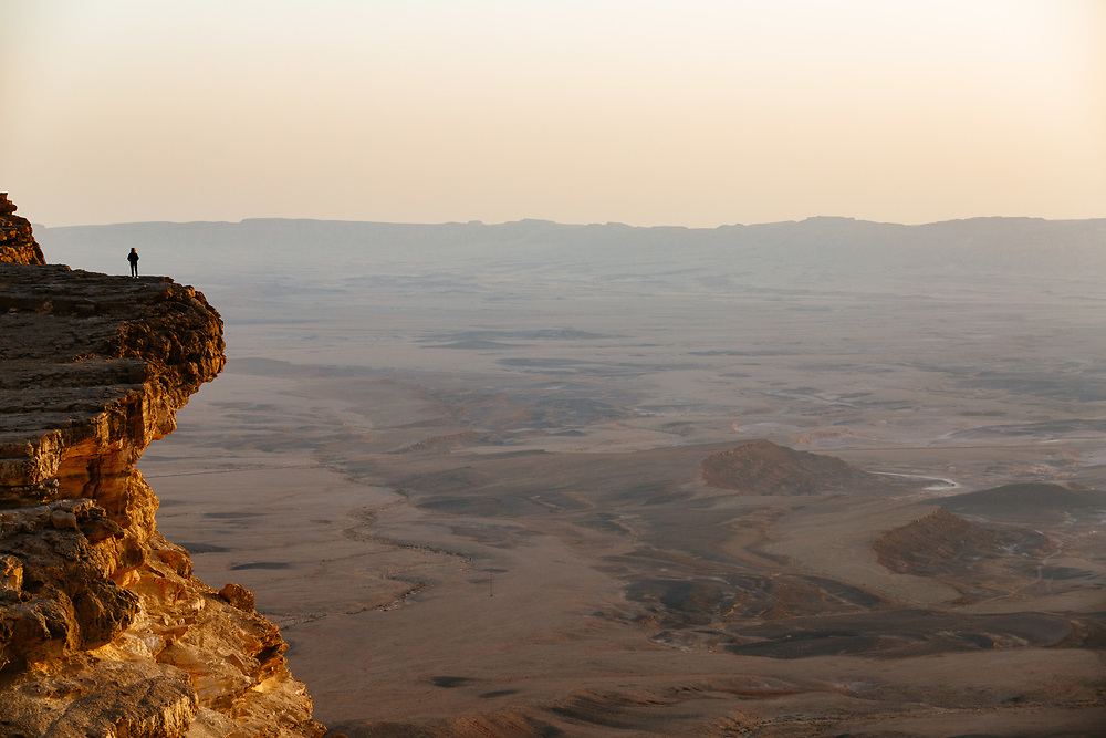 A woman watches the sunrise over the Ramon Crater (Makhtesh Ramon in Hebrew), the world's largest erosion crater in the Negev desert, southern Israel, on October 18, 2017.