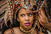 A dancers has final adkustments to her make up as she prepares for the parade - The Monday of the Notting Hill Carnival. The annual event on the streets of the Royal Borough of Kensington and Chelsea, over the August bank holiday weekend. It is led by members of the British West Indian community, and attracts around one million people annually, making it one of the world's largest street festivals.