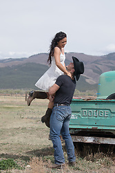 romantic cowboy and a girl together by a truck outdoors in a field cowboy holding a girl off the ground outdoors