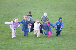 Multiracial group of children running around and having fun in the park,