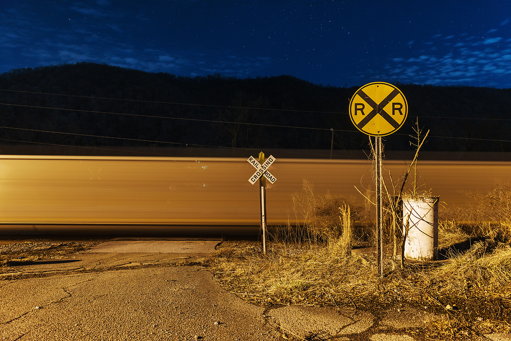 A passing train is blurred in a long exposure on railroad tracks alongside route 60 in Belle, West Virginia.