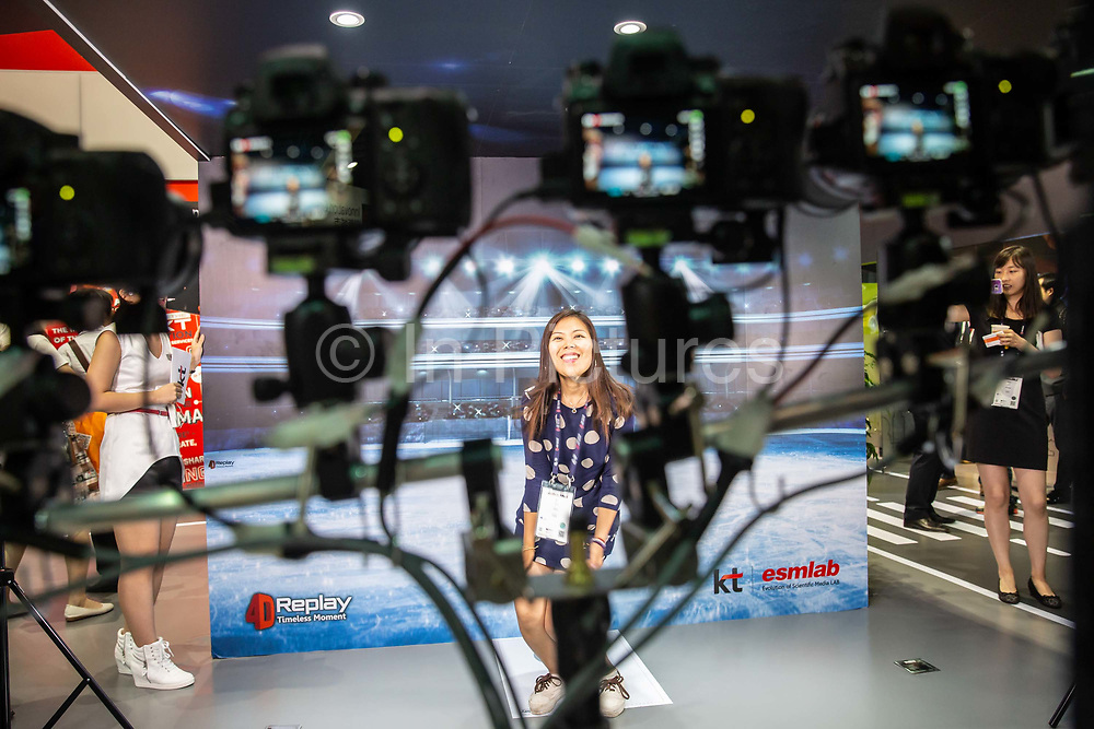 An attendant has her picture taken by a 360 degree surround ca,era system at the Mobile World Congress Shanghai in Shanghai, China, on Wednesday, June 29, 2016.