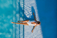 Aerial view of woman laying on the stairs of a swimming pool in a white swimsuit.