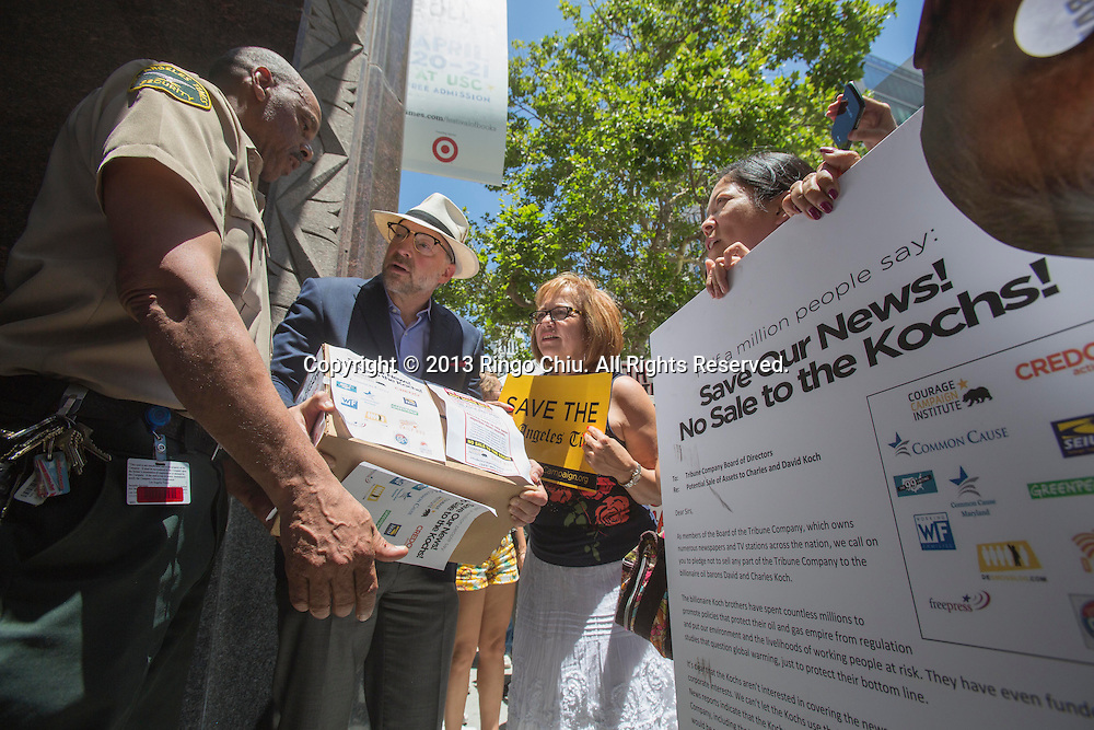 Activists with the ``Save Our News'' coalition deliver a 500,000-signature petition urging the Los Angeles Times management to reject any offers by the Koch Brothers to buy the newspaper outside the Los Angeles Times building on wednesday, May 29, 2013 in Los Angeles, California. (Photo by Ringo Chiu/PHOTOFORMULA.com)