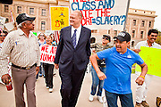 "14 MARCH 2011 - PHOENIX, AZ: TOM HORNE, Arizona's Republican Attorney General, is heckled by immigrants' rights supporters as he leaves the Arizona State Capitol in Phoenix Monday. Horne has supported toughening the state's anti-immigrant laws and eliminating ""ethnic studies"" programs in the state's public schools. Protests by immigrants' rights activists have continued as the state's conservative Republican legislators debate toughening the state's anti-immigrant bills. Some of the bills the state legislature has debated this year include eliminating birthright citizenship, a law that would require hospitals to check the immigration status of patients checking in for elective care, a bill that would require schools to verify the immigration status of students when they enroll and a bill that would require law enforcement to impound the cars of undocumented immigrants even if they have a legal driver's license from another state.      Photo by Jack Kurtz"