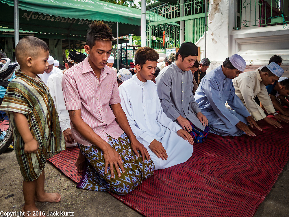 06 JULY 2016 - BANGKOK, THAILAND: Men pray during Eid services at Bang Luang Mosque in the Thonburi section of Bangkok. Eid al-Fitr is also called Feast of Breaking the Fast, the Sugar Feast, Bayram (Bajram), the Sweet Festival or Hari Raya Puasa and the Lesser Eid. It is an important Muslim religious holiday that marks the end of Ramadan, the Islamic holy month of fasting. Muslims are not allowed to fast on Eid. The holiday celebrates the conclusion of the 29 or 30 days of dawn-to-sunset fasting Muslims do during the month of Ramadan. Islam is the second largest religion in Thailand. Government sources say about 5% of Thais are Muslim, many in the Muslim community say the number is closer to 10%.        PHOTO BY JACK KURTZ