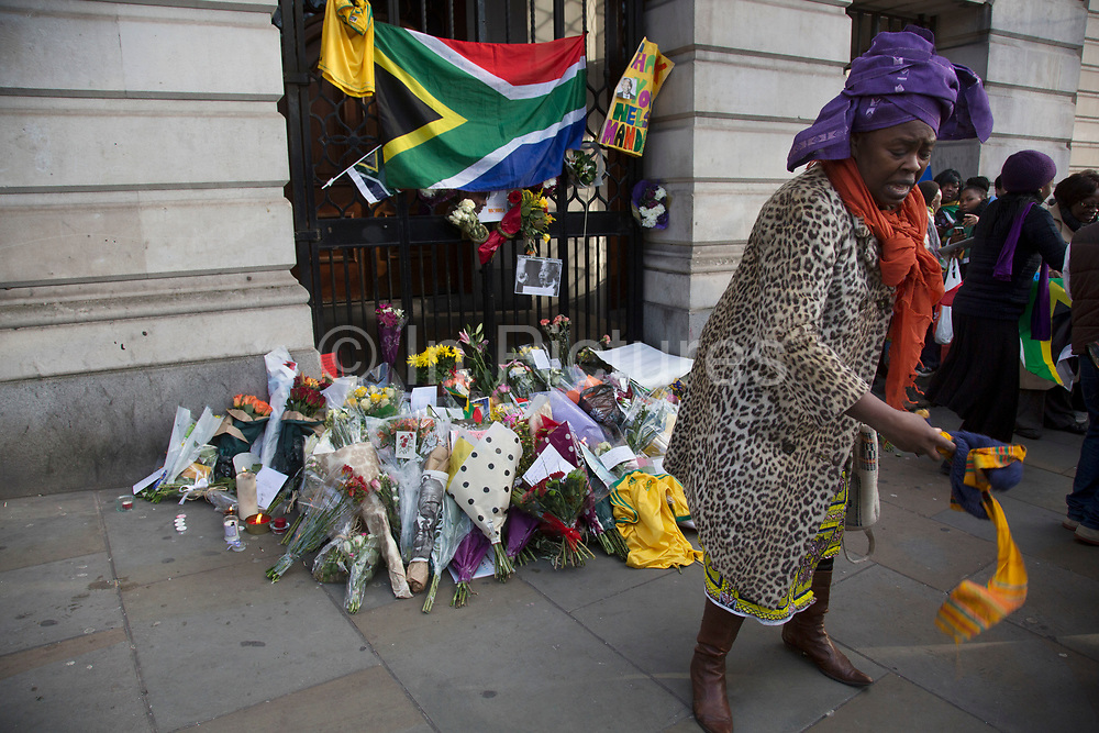 London, UK 6th December 2013: A woman blesses the ground near to the South African Embassy to pay tribute to former South African leader and anti-apartheid ANC campaigner Nelson Mandela, who died aged 95 on 5th December 2013.