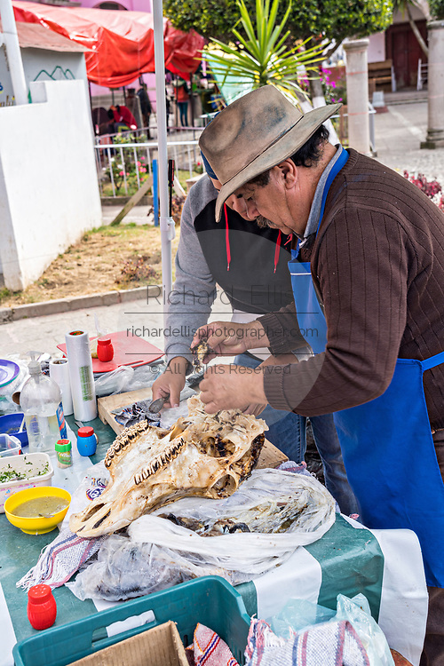 A vendor prepares tacos made with beef cheek meat off a cow skull on the Plaza de la Constitucion in Angangueo, Michoacan, Mexico. Angangueo is a tiny, remote mountain town and the entry point to the Sierra Chincua Monarch Butterfly Sanctuary.