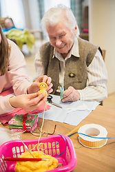 Senior woman with girl holding handmade crochet chick at rest home