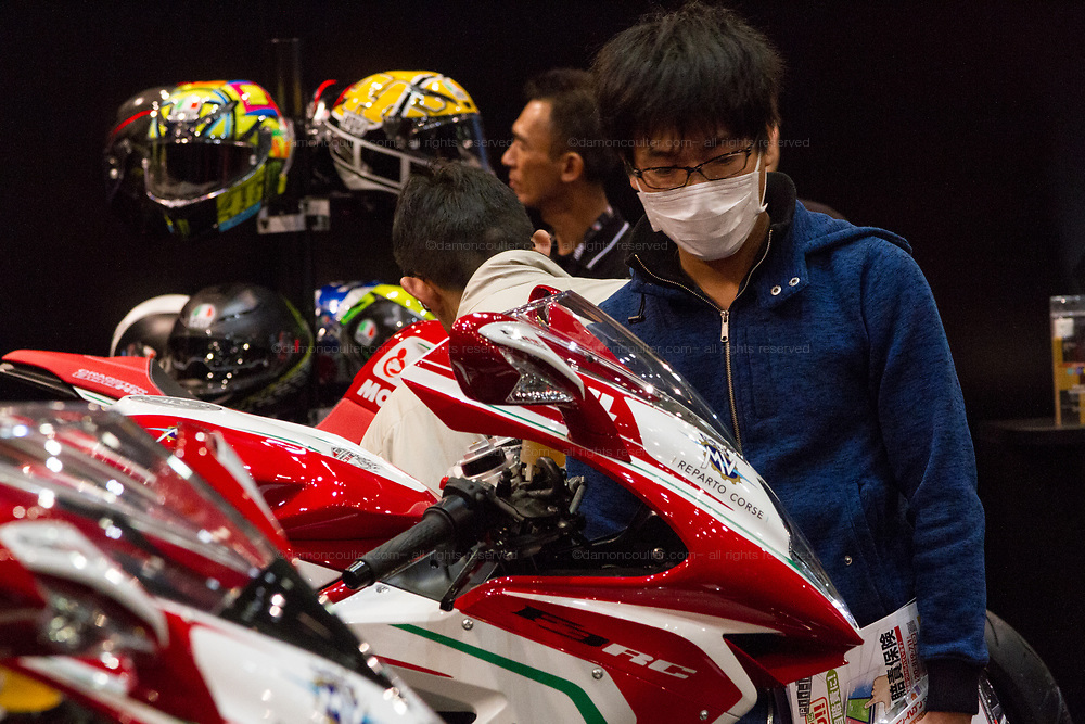 A man looks at motorbikes during the 44th annual Tokyo Motorcycle show. Tokyo Big Sight exhibition hall, Odaiba, Tokyo, Japan. Friday March 24th 2017. The show runs from Friday March 24th to Sunday March 26th and showcases technological innovations from all the main motorcycle manufacturers along with companies providing protective helmets pads and  clothing to decoration and even camping gear for bike-touring..