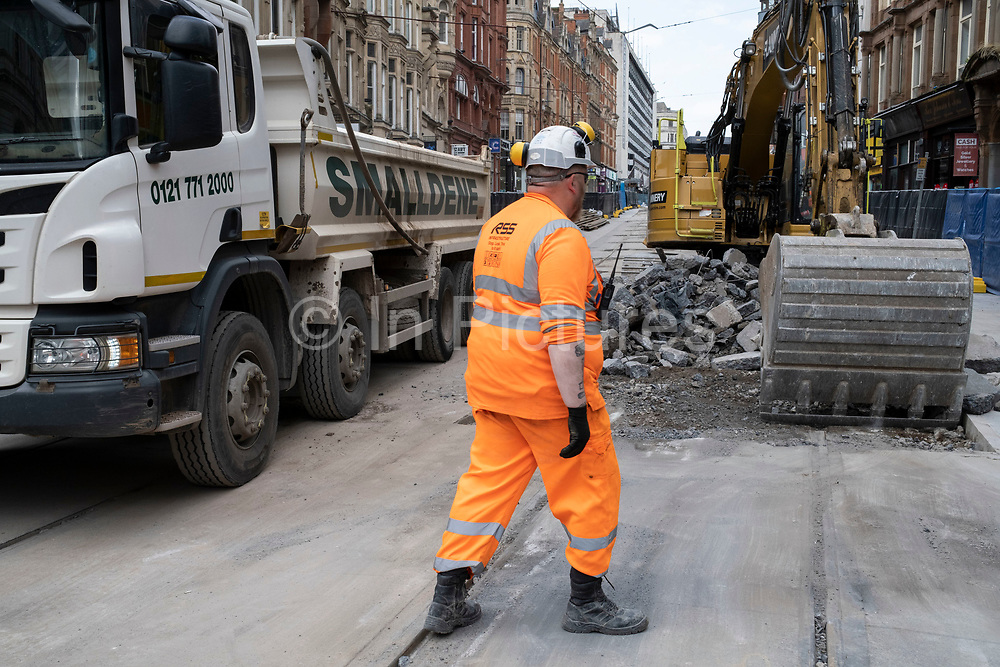 Team of workmen wearing orange high-viz overalls on a construction site work on the update to the Midland Metro tram public transport system in the city centre along Corporation Street on 3rd August 2021 in Birmingham, United Kingdom. The original tracks are being pulled up and relaid, while a new line is also under construction and due to open later in the year. The Midland Metro is a light-rail tram line in the county of West Midlands, England, operating between the cities of Birmingham and Wolverhampton via the towns of West Bromwich and Wednesbury. The line operates on streets in urban areas, and reopened conventional rail tracks that link the towns and cities. The owners are Transport for West Midlands with operation by National Express Midland Metro, a subsidiary of National Express. TfWM itself will operate the service from October 2018.