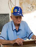 Elderly man playing dominos on a sidewalk, Havana, Cuba