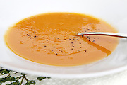 a plate of Orange Soup - Creamed Pumpkin and Sweet potato soup garnished with ground pepper