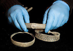 © Licensed to London News Pictures. 14/12/2011. LONDON, UK. A member of staff from the British Museum holds a bracelet from the Silverdale Viking Hoard found in September 2011 in north of England. The bracelet, discovered in Lancashire, was shown as part of the an exhibition at the museum highlighting the importance of the Treasure Act and Portable Antiquities Scheme and includes valuable finds from across the country. Photo credit: Matt Cetti-Roberts/LNP