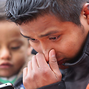 Father Constancio Garcia from Danbury cries while with his one year old son Damien at the shrine set up around the towns Christmas tree in Sandy Hook after the mass shootings at Sandy Hook Elementary School, Newtown, Connecticut, USA. 17th December 2012. Photo Tim Clayton