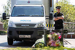 © Licensed to London News Pictures. 28/05/2018. Stockport, UK. A policeman stands beside flowers left at the scene outside The Salisbury Club on Truro Avenue in the Brinnington area of Stockport, Greater Manchester, where a car collided with pedestrians late last night, killing one man and injuring others.  A murder investigation has been launched. Police later recovered a black Audi A4 which fled the scene. Photo credit: Joel Goodman/LNP