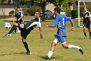 Nelson Martinez (L) of Deportivo Colomex controls the ball while competing with Team Shlama F.C. during National Soccer League play in Skokie, Il.  .