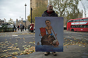 Political artist Kaya Mar with his latest painting  as demonstrators protest in Westminster on Budget Day on 22nd November 2017 in London, England, United Kingdom. As the Tories deliver their Autumn Budget, protesters make their views heard outside Parliament.