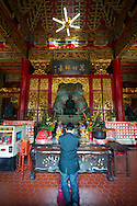 A devote prays to a Confucian Shrine at the Wenwu Temple at Sun Moon Lake, Taiwan.