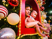 25 DECEMBER 2015 - SINGAPORE, SINGAPORE:  A man and his son in a display of Christmas themed holiday lights on Orchard Road in Singapore. Orchard Road is the heart of Singapore's upscale shopping and consumerism.    PHOTO BY JACK KURTZ