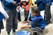 El Alto primary school. Pupils practise handwashing using a plastic bottle