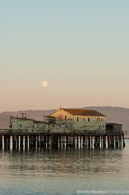 Full moon rising above pier at Pillar Point Harbor in Half Moon Bay, California