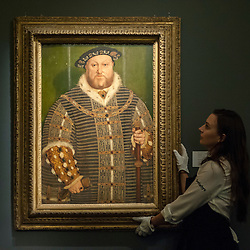 """© Licensed to London News Pictures. 04/12/2015. London, UK. A technician presents """"Portrait of Henry VIII"""" by Hans Holbein (est. £0.8-1.2 million), ahead of Sotheby's London evening sale of Old Master and British paintings on 9th December 2015. This is the last official image of his reign.  Photo credit : Stephen Chung/LNP"""