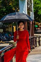 Vietnamese woman wearing traditonal Ao dai waling over a pedestrian footbridge, Hoi An, Vietnam.