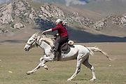 Woman galloping during a kiss chase (Kyz-Kuumai) competition at a traditional Kyrgyz horse games festival. Bosogo jailoo, Naryn province, Kyrgyzstan.