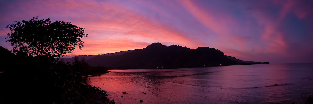 A panoramic of a dramatic sunset sky reflects on Kahana Bay on Oahu's windward coast in Hawaii