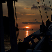 Sunset over the calm sea from a sailing boat.