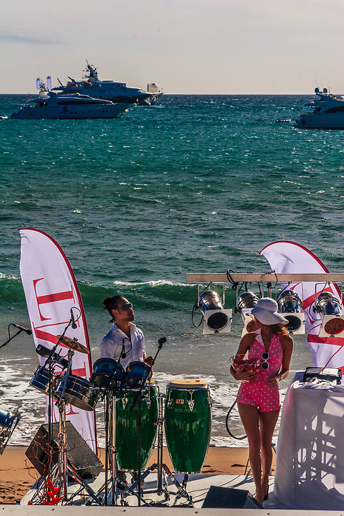 Music performance on Cannes beaches in France. Conguero plays Latin sounds with conga drums under hot Mediterranean sun.