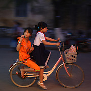 A street scene in Hoi An, Vietnam showing girls riding on a bicycle in the early evening. Hoi An is an ancient town and an exceptionally well-preserved example of a South-East Asian trading port dating from the 15th century. Hoi An is now a major tourist attraction because of its history. Hoi An, Vietnam. 5th March 2012. Photo Tim Clayton