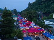 View of Luang Prabang night market in the early evening, Lao PDR.  The traders in the night market are 80% Hmong ethnic minority, almost all of whom are women who sell cotton embroidery and applique work. Many Hmong have moved to Luang Prabang in response to government pressure to end opium production and curtail slash and burn agriculture and to take advantage of educational opportunities for their children.