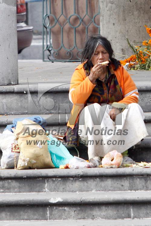 TOLUCA, México.- Después de haber sido desmanteladas las ofrendas por el día de Muertos instaladas en la Plaza González Arratia, indigentes aprovecharon la comida que fue retirada. Agencia MVT / Crisanta Espinosa. (DIGITAL)