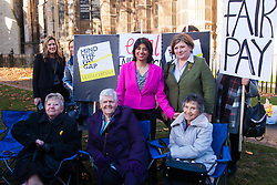 Westminster, London, December 16th 2014.  Gwen Davis, Sheila Douglass and Vera Sime, all seated, who were amongst the original Ford Dagenham workers to strike for equal pay, pose for pictures outside Parliament.