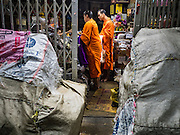 """21 DECEMBER 2015 - BANGKOK, THAILAND:  Buddhist monks collect alms from a shopkeeper in Pak Khlong Talat, also called the Flower Market. The market has been a Bangkok landmark for more than 50 years and is the largest wholesale flower market in Bangkok. A recent renovation resulted in many stalls being closed to make room for chain restaurants to attract tourists. Now Bangkok city officials are threatening to evict sidewalk vendors who line the outside of the market. Evicting the sidewalk vendors is a part of a citywide effort to """"clean up"""" Bangkok.      PHOTO BY JACK KURTZ"""