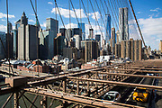 Cars and an iconic yellow taxi drive across Brooklyn Bridge away from Lower Manhattan, New York City, United States of America.  The bridge's cables form a distinctive weblike pattern.