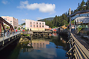 Alaska, Ketchikan. Walking tour of the historic Ceek Street district built over water with a view towards more modern buildiings.